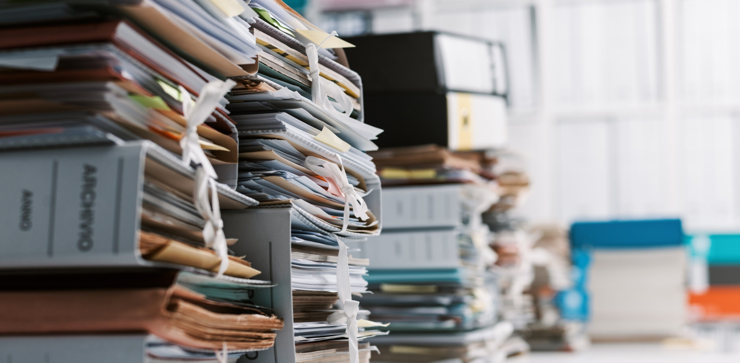 Stacks of paperwork and files in the office: work overload, files management and administration concept