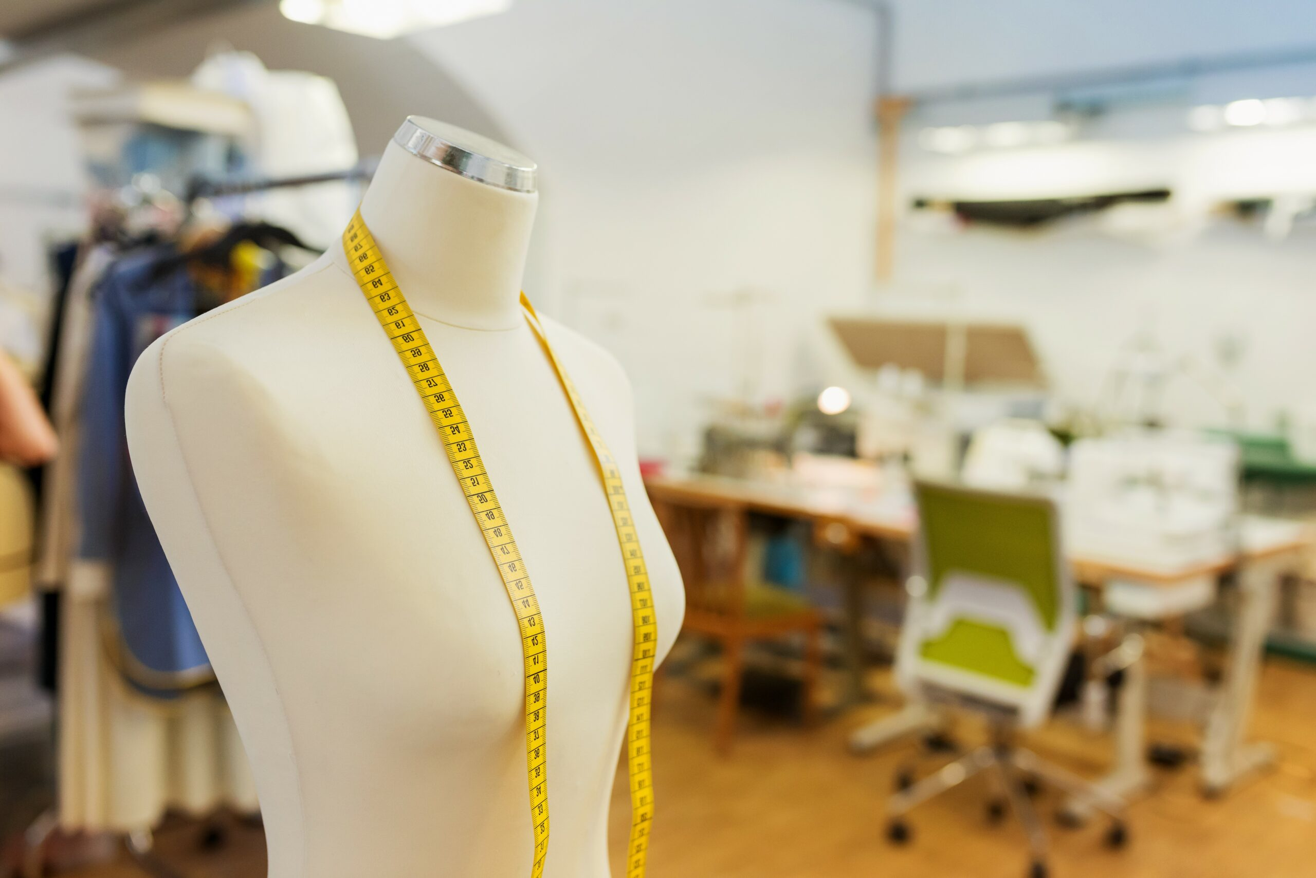 Tailors white textile dummy with yellow measure tape